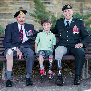 veterans and child sitting on a bench