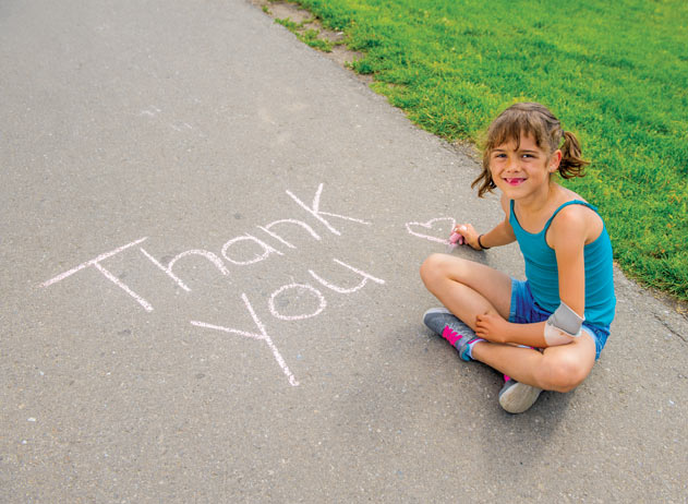 "A young amputee girl wearing a prosthetic arm writing ""thank you"" in chalk on a sidewalk."