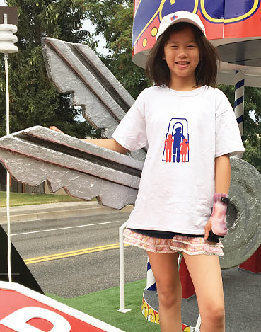 A child amputee standing on The War Amps PLAYSAFE/DRIVESAFE float during a parade.