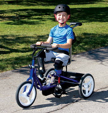 Dylan, a double leg amputee, wearing his artificial legs and riding his adaptive three-wheeled bicycle.