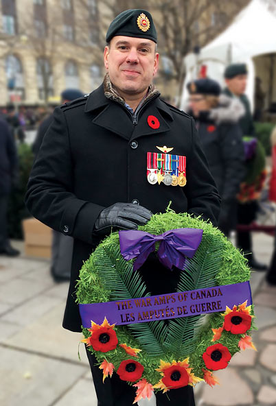 Retired sergeant Gaétan, a leg amputee, holding a wreath at a Remembrance Day ceremony.