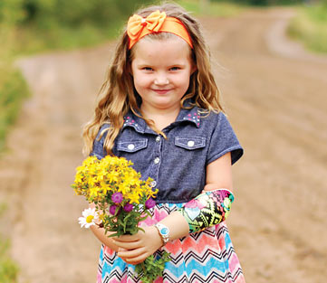 Jaelynn, a left arm amputee, holding a bouquet of beautiful wildflowers using her myoelectric arm.