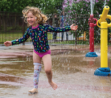 Child amputee Jeanne wearing her water leg while playing at a splash pad.