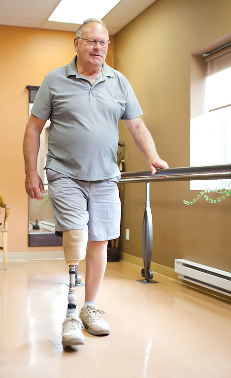 A male amputee wearing a prosthetic leg and walking alongside a parallel bar.