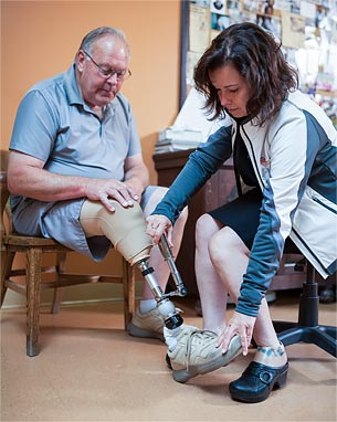 A male amputee receiving adjustments to his prosthetic leg by a prosthetist.